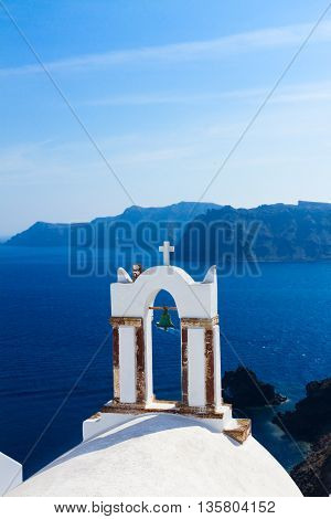 white church belfry, sea waters and volcano caldera, beautiful details of Santorini island, Greece