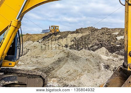 Earth mover is moving earth outdoors leveling ground. View under the arm of excavator.