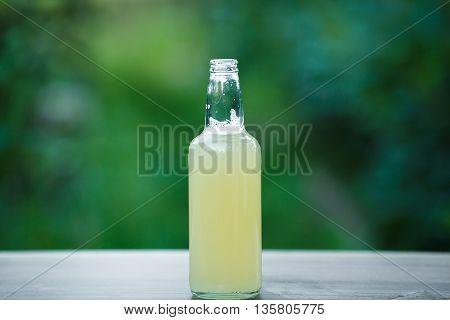 homemade lemonade in glass bottle on bokeh background. Lemon beer.