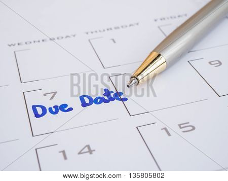 Close up handwriting word Due Date and pen on calendar desk (Selective focus)