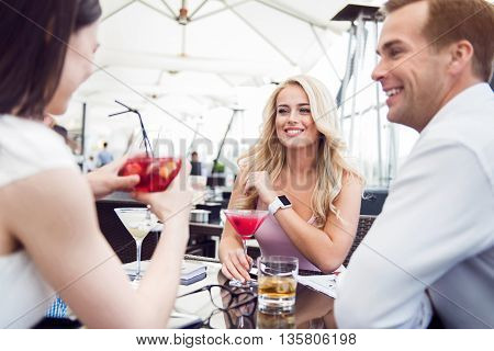 Pleasant relaxation. Pleasant cheerful smiling friends sitting at the table and restring in the cafe while expressing joy
