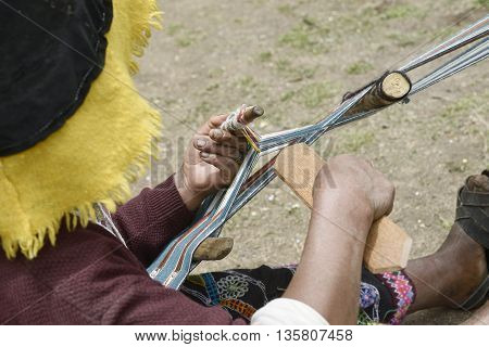 Peruvian woman in traditional clothing weaving cloth on a hand loom in the Andes Mountains Peru