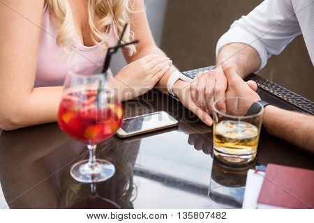 Real feelings. Pleasant loving couple sitting at the table and holding hands together while resting