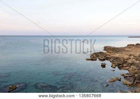 Photo of sea in protaras cyprus island with rocks and a boat at sunset.