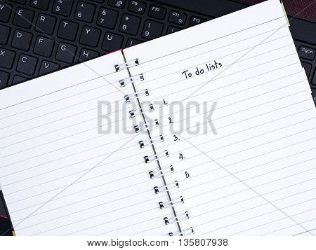 Handwriting to do list on notebook with laptop keyboard