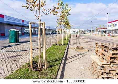 Zrenjanin Vojvodina Serbia - 09. October 2015: Garden Worker is cleaning new parking place ending works at shopping mall