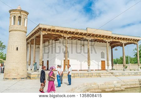 BUKHARA UZBEKISTAN - APRIL 29 2015: The Khakim Kushbegi Mosque with the separately standing brick minaret and slender wooden pillars around the prayer hall on April 29 in Bukhara.