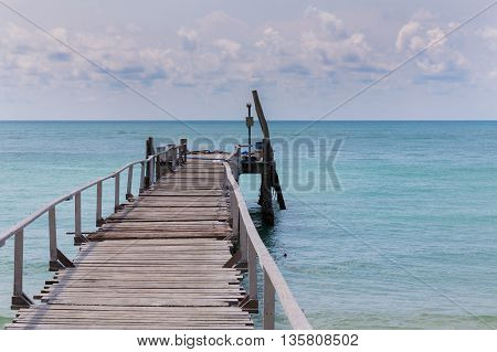 Wooden walking way leading to the seacoast, natural landscape background