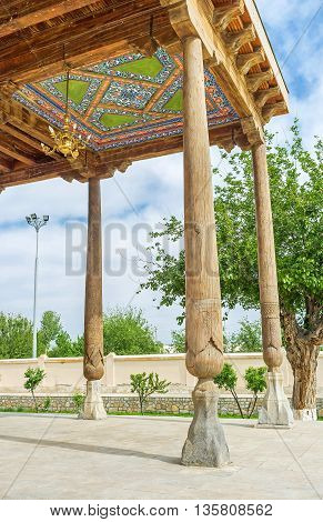 The wooden terrace of Khakim Kushbegi Mosque decorated with the carved wooden pillars and paintings on the roof Bukhara Uzbekistan.