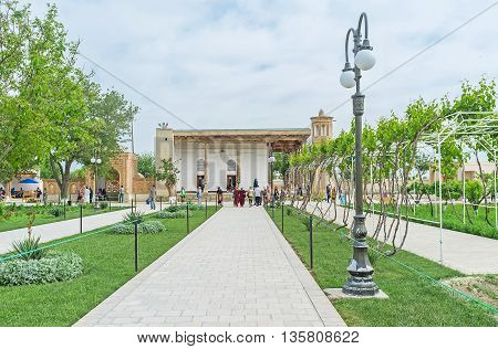 BUKHARA UZBEKISTAN - APRIL 29 2015: The beautiful green street decorated with the flower beds leads to the Khakim Kushbegi Mosque the part of Bahauddin Nakshbandi complex on April 29 in Bukhara.