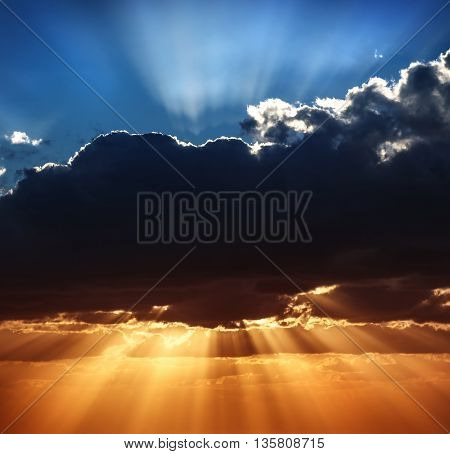 Beautiful heaven landscape, blue and yellow sky, amazing view on sun rays breaking through big dark clouds, beauty of wonderful nature