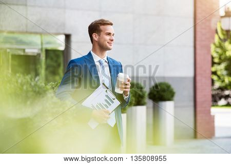 Confident vision. Pleasant handsome delighted man holding folder and drinking coffee while standing near office building