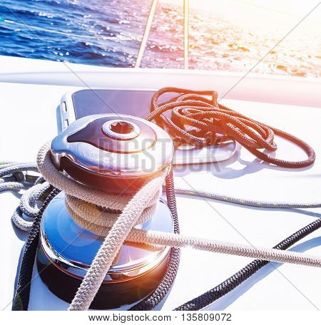 Crank handle of sailboat, detail of yacht, holder for rope, bright sunset in the sea, summer holidays, luxury water transport, yachting sport concept