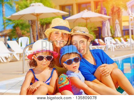 Mother with kids relaxing on beach resort, sitting near poolside, active summer holidays, young tourists, happy family concept