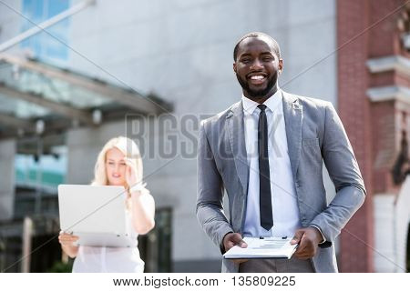 Full of positivity. Cheerful delighted smiling man holding folder and standing near office building while pleasant woman using laptop in the background