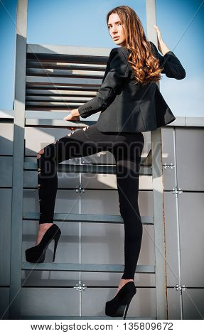 Outdoor fashion shot: sexy beautiful young woman in pants jacket and shoes standing on a ladder