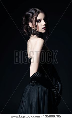 Dramatic portrait of a beautiful sad goth girl among the dark. Rear view