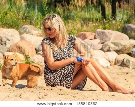 Happy woman sun tanning and relaxing on beach. Joyful girl in sunglasses with dog resting at sea. Summer relax and happiness.