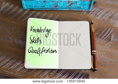 Handwritten Text Knowledge Skills Qualifications over notebook, copy space available