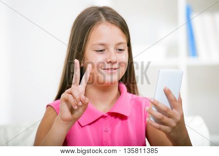 Smiling deaf girl talking using sign language on the smartphone's cam