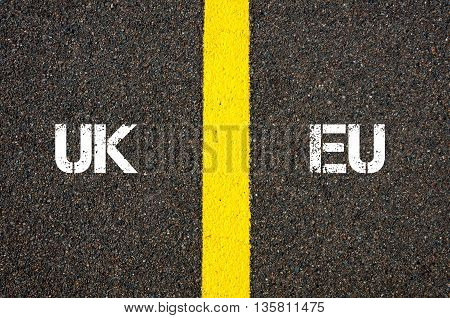 Antonym concept of UK United Kingdom versus EU EUROPEAN UNION written over tarmac road marking yellow paint separating line between words