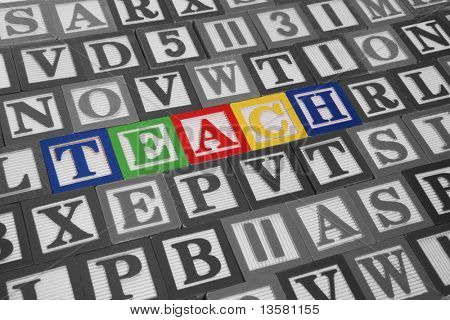 Colorful toy blocks spelling out the word teach