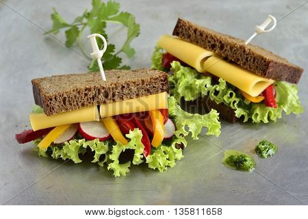 Rye sandwich with cheese vegetables and pesto