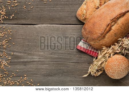 Bread and and wheat on a wooden table