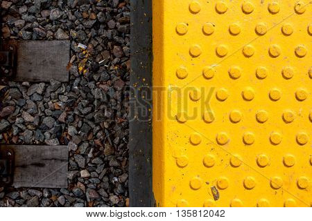 Yellow warning tiles with relief and sleeper railway