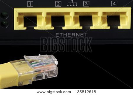 foreground of a yellow network cable and four network ports at the bottom