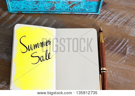 Text Summer Sale over notebook, copy space available