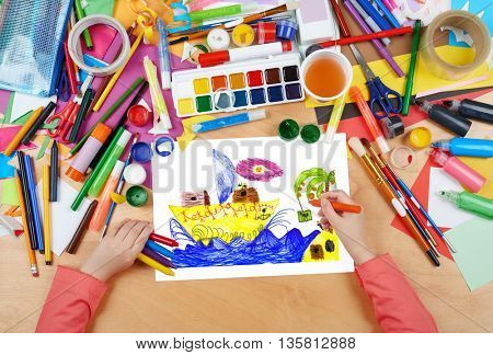 retro sailing ship near island with palm tree, child drawing , top view hands with pencil painting picture on paper, artwork workplace