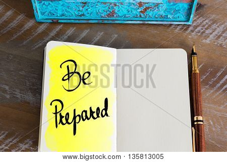 Text Be Prepared handwritten over notebook, copy space available