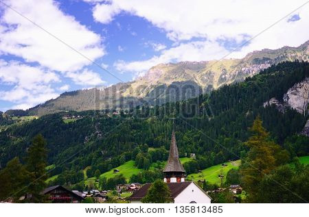 Tourist Town of Lauterbrunnen in Lauterbrunnen Valley (Jungfrau Region, Switzerland). Church in the Foreground. Mountain Slopes in the Background.
