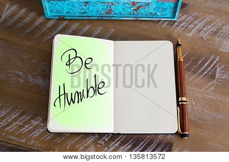 Handwritten Text Be Humble over notebook, copy space available