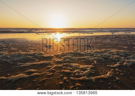 Sea foam during sunset on the shores of the North Sea.