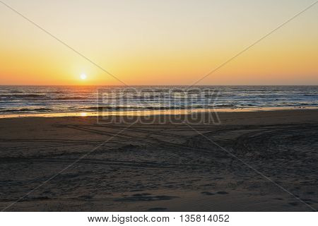 tire tracks on the beach during sunset