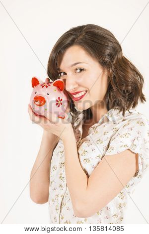Close up portrait of happy young beautiful woman with pink piggy bank, studio shot on white background