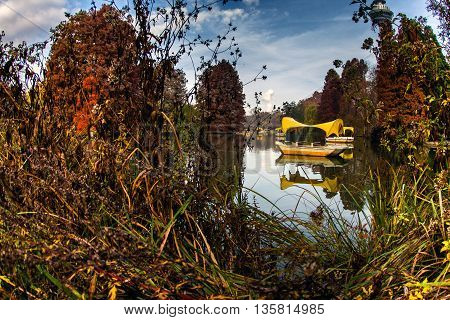 a yellow boat in a lake with water and surrounded by nature