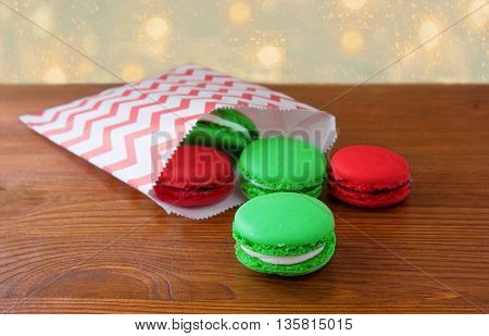 Colorful French Macarons on wooden background. Christmas concert.