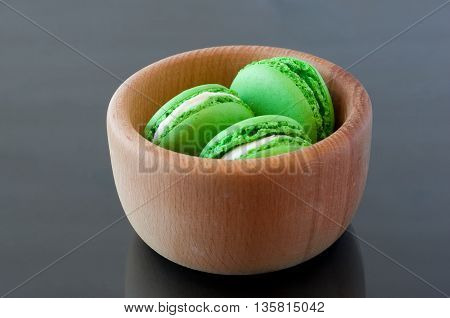 French Macarons in a wooden bowl on a dark background