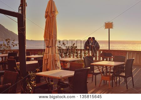 Camogli, Ligure, Italy - 07 November 2015: young  couple by the sea in feelings of love.  On the waterfront of the Mediterranean Sea in Camogli, photo captured in an urban environment Camogli, Ligure, Italy.