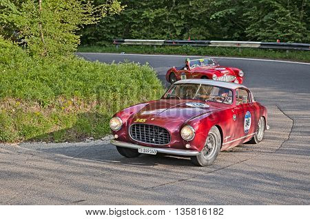 PASSO DELLA FUTA (FI) ITALY - MAY 21: driver and co-driver on a rare classic car Ferrari 250 Europa GT Pininfarina (1955) in italian historical race Mille Miglia on May 21, 2016 in Passo della Futa (FI) Italy
