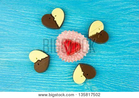 chocolate candies in a heart shape on a turquoise background