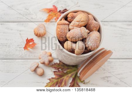 Delicious homemade cookies in the form of a acorns, mushrooms, cones and flowers on wooden background.