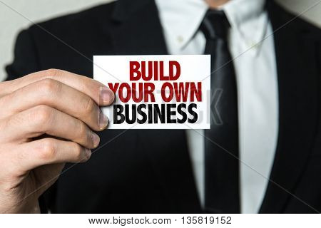 Business man holding a card with the text: Build Your Own Business