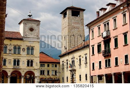 Belluno Italy - June 8 2006: Late 15th century Rector's Palace (left) and Renaissance houses with a stone watch tower in the Piazza dei Duomo