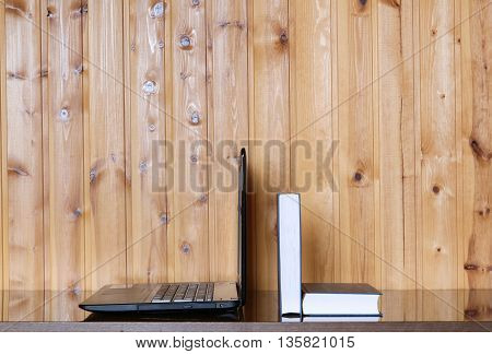Book and Laptop on a wooden table. Wood background. E-learning. Education. Internet labrary.
