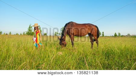 Little girl in  bright dress and hat walking on the meadow with  horse