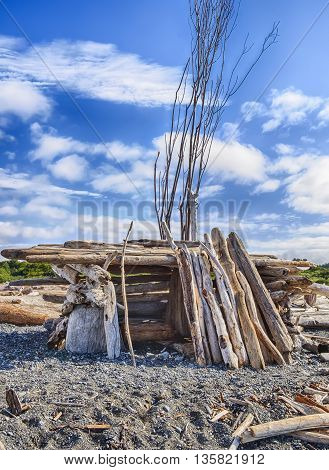 A small homemade structure with an entrance built out of driftwood on a beach in Puget Sound provides shelter from the wind.